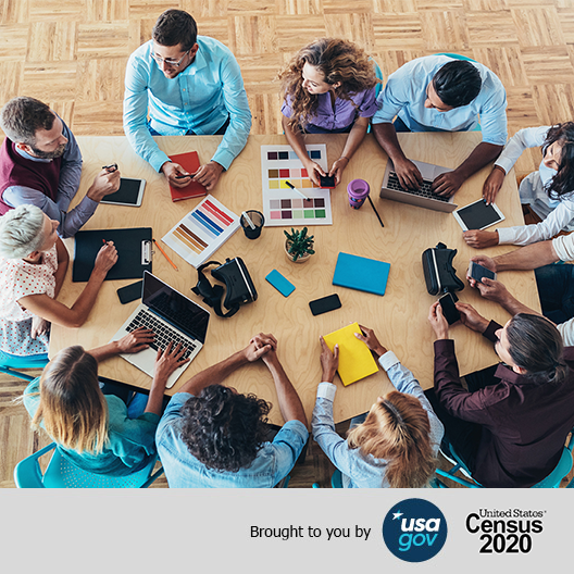 Group of people around a table. Group of people talking around an office table. Brought to you by USAGov United States Census 2020