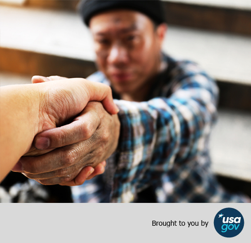 Helping hand reaching out to a man. Brought to you by USAGov.