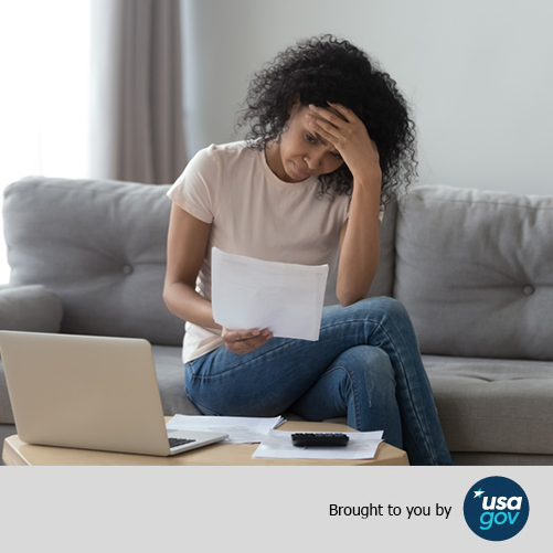 A stressed woman holds her head looking at bills on her couch